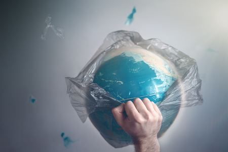 A man breaks a garbage bag which is wrapped globe of planet Earth. The concept of ecology and pollution of the surrounding environment. Copy space and tint. Zdjęcie Seryjne - 124181403