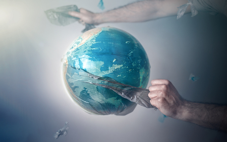 Men's hands tear off a plastic bag from the globe of planet Earth. The concept of environmental protection. Eco. Tint and copy space. Zdjęcie Seryjne - 124181404