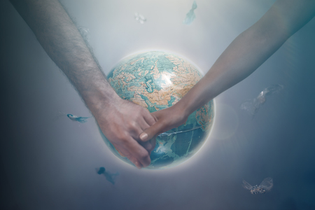 A man and a woman of different races holding hands on the background of the globe of the planet Earth. The concept of international Association for the preservation of the environment. Tint. Zdjęcie Seryjne - 124181407