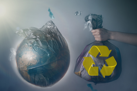 A womans hand holds a garbage bag next to the globe of planet Earth. Concept of ecology and environmental protection. The recycle sign. Tint.