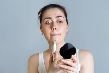 A young pretty woman looks in the mirror and disguises rashes on her face. The concept of acne, growing up and cosmetology. Copy space and gray background. Stock Photo