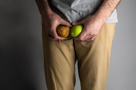 A man in beige jeans at the level of the , holding a ripe and rotten apple. Disease for men. The concept of protection of sexually transmitted infections. Testicular cancer.