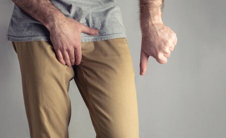 A man in beige jeans holds his and points with his thumb down. Disease for men. The concept of protection against sexually transmitted infections. Testicular cancer.