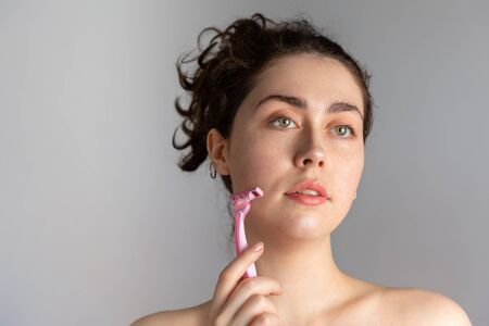 Beautiful young woman holding a razor in her face. The concept of getting rid of unwanted facial hair. Copy space.