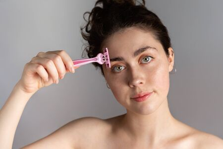 A beautiful young woman holds a razor to her eyebrow. The concept of getting rid of unwanted facial hair. Stock fotó - 138386056