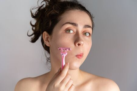 A beautiful young woman holds a razor to her cheek. The concept of getting rid of unwanted facial hair. Stock fotó - 138386055