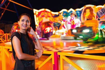 Young beautiful woman having fun in the amusement Park. Concept of entertainment and summer festivals. 版權商用圖片