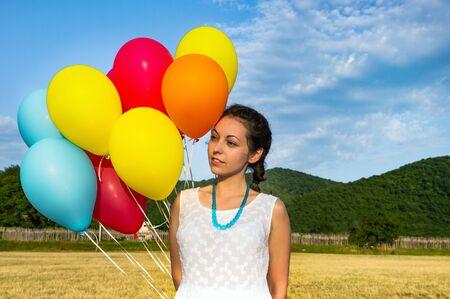Carina giovane donna in abito bianco con palloncini in mano. Il concetto di libertà e gioia. Avvicinamento