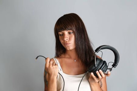 Beautiful young woman with tattoos and piercings, holding headphones and a wire with a connector on the end