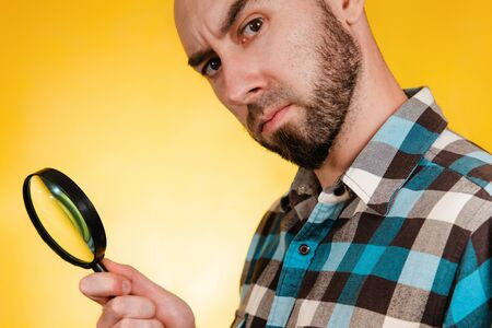 The concept of finding and solving problems. A bald man with a beard, dressed in a blue plaid shirt, holding a magnifying glass and looking intently. Copy space.