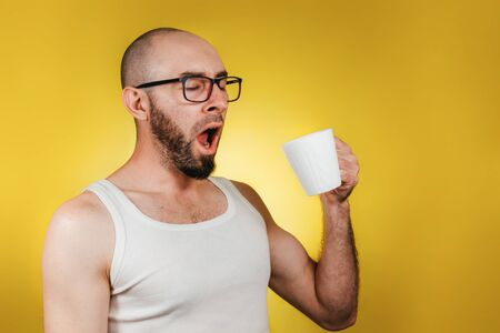 Concept of morning awakening and productivity. A bald, bearded man with glasses, holding a mug of coffee or tea and yawning lazily. Yellow background. Copy space. Banco de Imagens