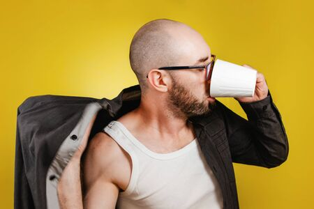 The concept of morning awakening and productivity. A bald, bearded man wearing glasses, wearing a shirt and drinking coffee or tea from a mug at the same time. Yellow background. Close up Reklamní fotografie