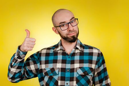 People and emotions. A bald, bearded man wearing glasses and a blue checked shirt, giving a thumbs-up. Yellow background. Close up