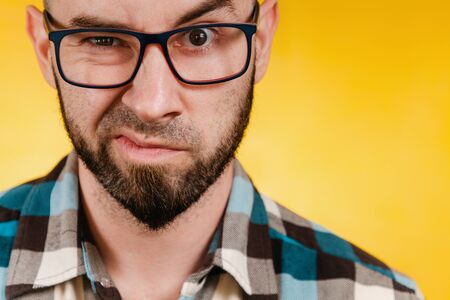 People and emotions. A bearded man wearing glasses and a blue checked shirt expresses his dislike. Yellow background. Close up Reklamní fotografie
