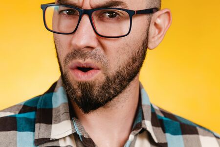 People and emotions. A bearded man with glasses and a blue checked shirt asks something in a dissatisfied voice. Yellow background. Close up