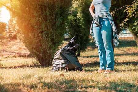 The concept of environmental pollution and Earth day. A woman volunteer removes garbage in the Park, near the feet is a black garbage bag. Copy space.