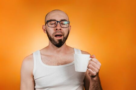 Concept of morning awakening and productivity. A bald, bearded man with glasses, holding a mug of coffee or tea and yawning lazily. Orange background. Copy space.