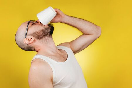 The concept of morning awakening and productivity. A bald, bearded man with glasses, drinking a mug of coffee or tea in one gulp. Yellow background. Copy space.
