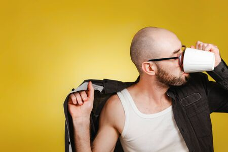 The concept of morning awakening and productivity. A bald, bearded man wearing glasses, wearing a shirt and drinking coffee or tea from a mug at the same time. Yellow background. Copy space. Banco de Imagens