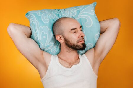 The concept of rest. Man, folding his hands under his pillow, sleeps overuses to the side. Orange background. Stockfoto