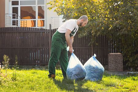 Gardener picks up bags of leaves to remove debris from the territory. Green uniform.