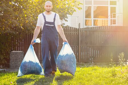 The gardener smiling and removes the bags of compost. Light. Blue uniform.