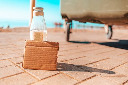 The concept of environmental pollution and waste sorting. Glass bottle with empty cardboard. Bin and quayside on the background. Copy space.