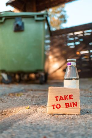 The concept of environmental pollution and waste sorting. A glass bottle stands on the ground in front of a dumpster. Near cardboard with the inscription TAKE to BIN. Vertical orientation.