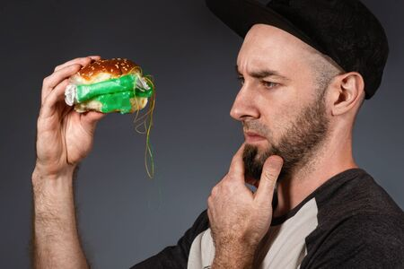 The concept of fast food and ecology. A man in a cap and a beard, holding a hamburger, and cautiously examines its plastic filling. Black background. Close up.