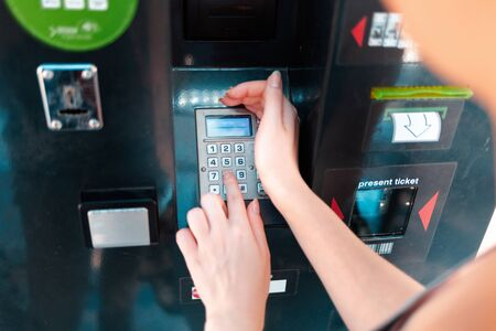 ATM and banking operations. The woman, covering his hand, enters the password from the Bank card. Stock Photo