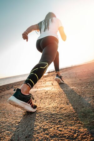 Sports and Jogging along the sea. The woman stands ready to run. In the background, mountains and a narrow strip of sea. Bottom view. Vertical.