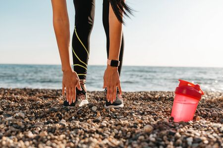 Concept of sport and healthy lifestyle. A woman in sportswear is stretching, a shaker is lying next to her. In the background, the sea and the sky. Copy space. Reklamní fotografie