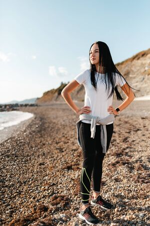 Concept of sport and healthy lifestyle. A young woman in sportswear, posing on a rocky beach and looking into the distance. Vertcical.