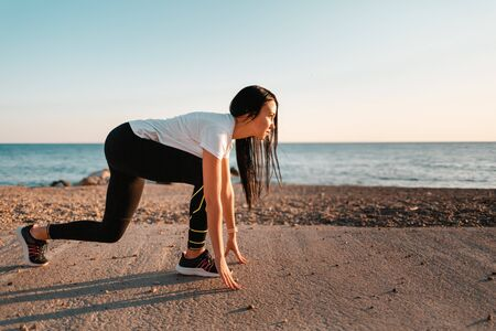 Sports and Jogging along the sea. A young brunette woman stands ready to run. In the background, the sea and the rocky shore.Copy space. Stock fotó