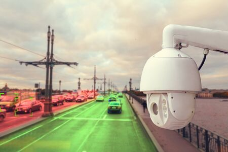 The concept of video surveillance and security technology. A surveillance camera monitors the violators of traffic rules. In the background, the road of different congestion, red and green colors.