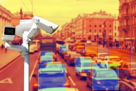 The concept of video surveillance and security technologies. Surveillance camera on the background of the city road with cars. Definition zone. Tint.