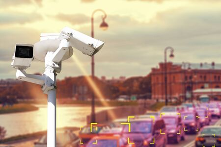 The concept of video surveillance and security technology. CCTV camera on the background of a road bridge with traffic in cloudy weather with a Sunny sunset. Color definition zone. Imagens - 132292052