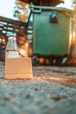 The concept of environmental pollution and waste sorting. A glass bottle stands on the ground in front of a dumpster. Near cardboard. Vertical orientation.