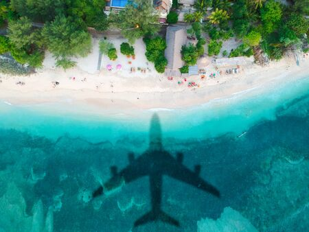 The concept of travel and air travel. Top view of the sandy coast of the ocean, with the shadow on the water from the landing plane. Airplanes shadow at the down side. Copy space. Stok Fotoğraf