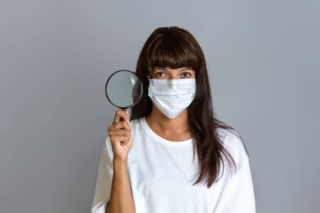 Medicine and research. A woman doctor in a coat and with a mask on her face holding a magnifying glass. Copy space