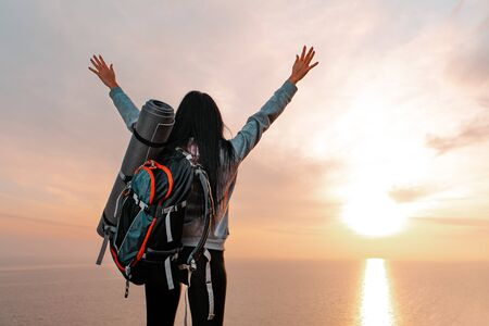 Tourism and sports recreation. The concept of success. A young woman with a tourist backpack behind her back, raises her hands up joyfully. Sunset. Copy space.