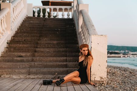 Sexy blonde in a black dress and hat posing sitting on the steps. In the distance you can see the sea. Stock fotó
