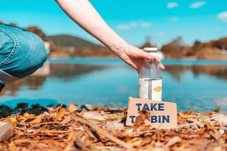 Protection of the environment and Earth Day. A female volunteer picks up a glass bottle containing a cardboard with the words: take to bin
