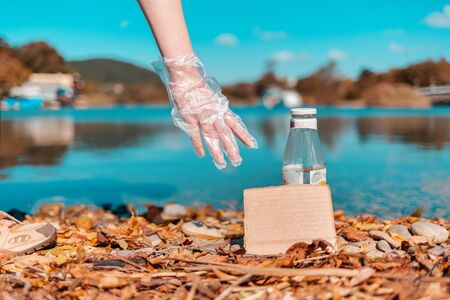 Protection of the environment and Earth Day. A female volunteer picks up a glass bottle, near which lies an empty cardboard. Copy space.