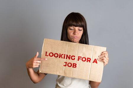 Business and advertising. A young brunette with a piercing holding a cardboard with text LOOKING FOR A JOB and points a finger at it. Gray background.