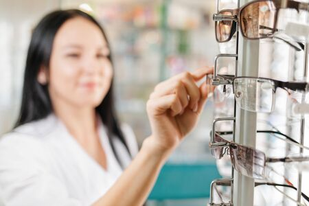 Medicine, pharmacy and optics. A brunette woman in a white coat takes off her glasses with her hands from the window. Close-up of glasses. Blurred background Foto de archivo