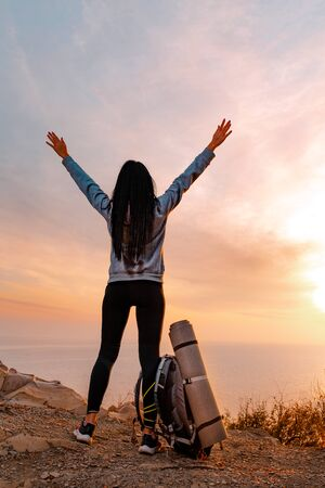 Tourism and sports recreation. The concept of success. A young woman with a tourist backpack near her feet, raises her hands up joyfully. Sunset. Vertical orientation. Banco de Imagens