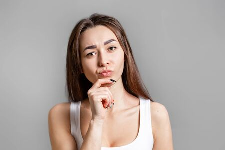 The concept of searching for ideas and information. Portrait of a pensive young Caucasian woman with her hand resting on her chin. Gray background. Copy space.