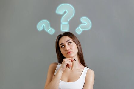 The concept of searching for ideas and information. Portrait of thoughtfully young Caucasian woman looking up at question marks. Gray background. Copy space.