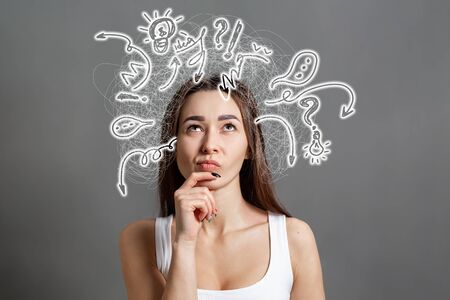 The concept of searching for ideas and information. Portrait of a pensive young Caucasian woman looking up, with painted icons above her head, Gray background. Copy space.